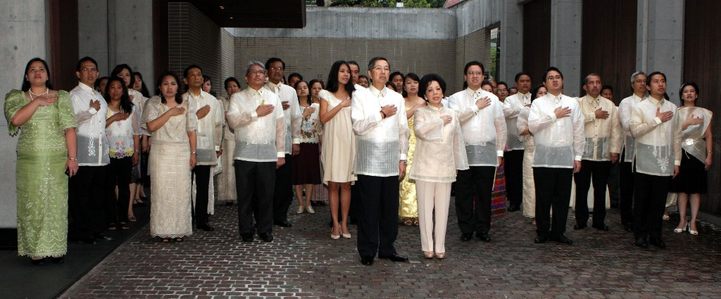 Amb. and Mme. Manuel M. Lopez leads the personnel of the Philippine Embassy in Tokyo in singing the Philippine National Anthem.