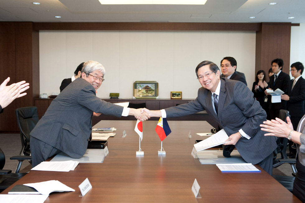 Ambassador Manuel M. Lopez and JICA Vice President Izumi Arai shake hands after signing ceremonies for seven ODA projects.