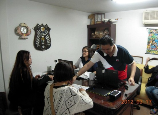 (Okinawa, Japan) Embassy personnel as VRM operators assist two Filipinas in their registration.